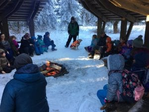 JCCS students sitting around the outdoor camp fire